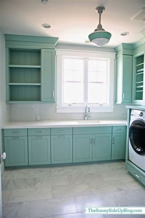 Beautiful laundry room features teal cabinets painted